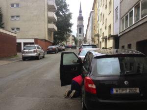Mann kriecht in Fahrerfussraum