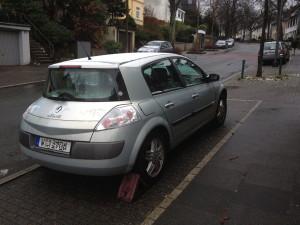 auto_bergauf_geparkt_wegrollen_radkeil_bremskeil