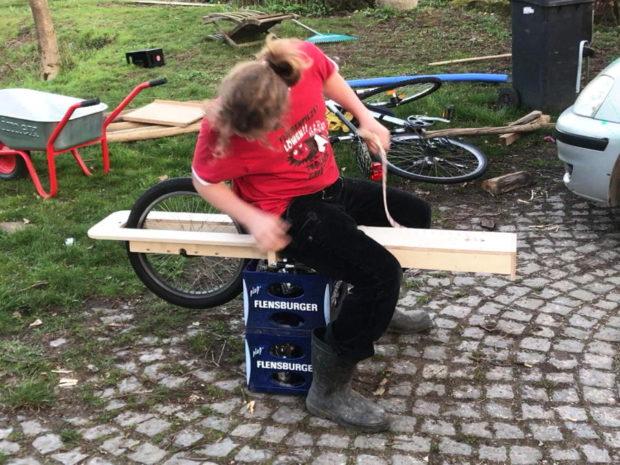 Person sitzt auf Holz