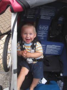 Glückliches, schokokeksverschmiertes Kleinkind in Kinderanhänger