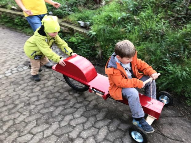 Zwei Kinder auf einem Ruderrenner