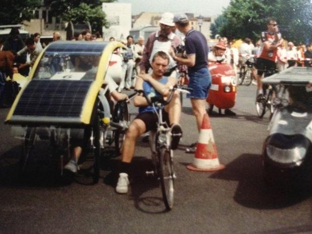 Mann auf Liegerad mit kurzen Hosen zwischen Solarmobilen mit Solarzellen-Bedeckung