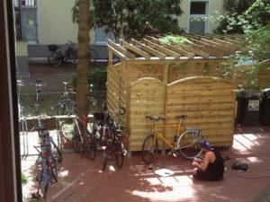 Mann sitzt im Berliner Hinterhof vor Fahrrad