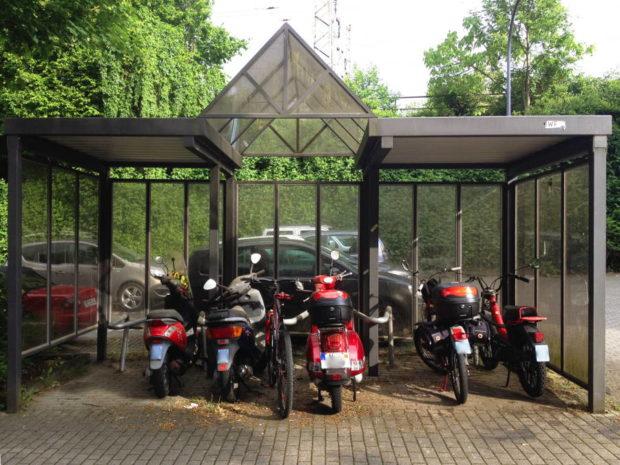 Ein Fahrrad und 5 Mopeds an einem Fahrradständer