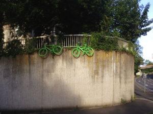 Grüne Fahrräder an Stützmauer