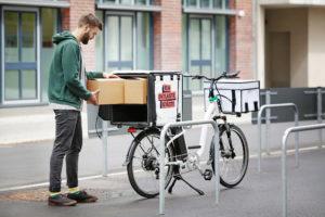 Jüngling hinter Lastenrad mit Pappkarton in der Hand