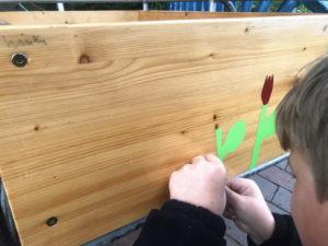 Kind klebt Folien auf Holz