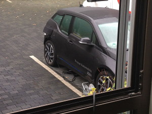 manko_von_bmw_i3_aufladen_von_elektrofahrzeug_mit_verlaengerungskabel_durch_fenster_auf_parkplatz