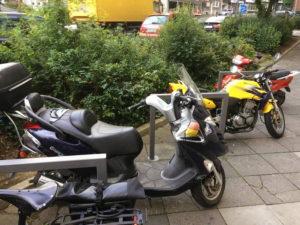 Motorroller und Motorrad in Fahrradbügeln