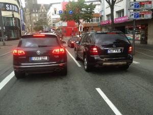Konformisten-Kutschen schwarze SUVs nebeneinander vor der Ampel