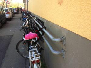 Fahrräder an Rohren an einer Wand anschlossen